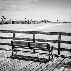 Seal Beach California pier bench black and white photo with the Pacific Ocean and oceanfront homes. Seal Beach is in Orange County Southern California in the United States of America.