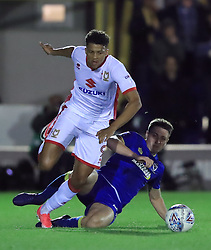 Milton Keynes Dons' Osman Sow, left battle for the ball with AFC Wimbledon's Anthony Hartigan, right