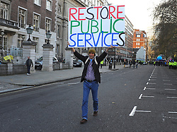 © Licensed to London News Pictures. 30/11/2011, London, UK. A man walks down a street with a sign saying restore public services. Up to two million public sector workers are staging a strike over pensions in what is set to be the biggest walkout for a generation. Photo credit : Stephen Simpson/LNP