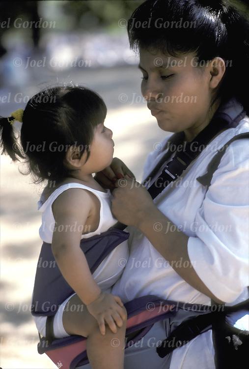 Hispanic American mother outdoors carrying toddler making eye contact
