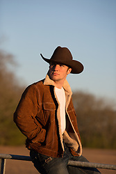 sexy cowboy at sunset in a sheepskin and suede jacket outdoors on a fence