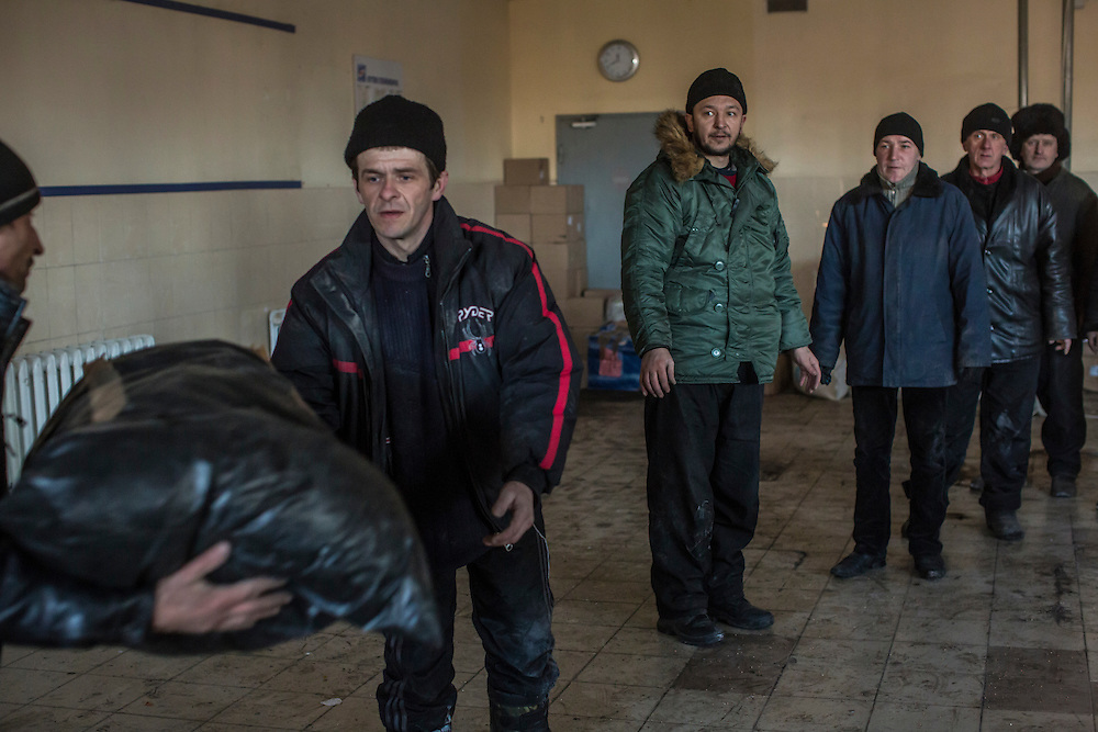 DEBALTSEVE, UKRAINE - FEBRUARY 20: Local residents unload humanitarian aid from a truck into an empty supermarket on February 20, 2015 in Debaltseve, Ukraine. Ukrainian forces withdrew from the strategic and hard-fought town after being effectively surrounded by pro-Russian rebels, though fighting has caused widespread destruction. (Photo by Brendan Hoffman/Getty Images) *** Local Caption ***