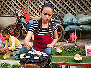 "13 MARCH 2016 - LUANG PRABANG, LAOS: A woman makes grilled quail eggs, an Asian delicacy, in the market in Luang Prabang. Luang Prabang was named a UNESCO World Heritage Site in 1995. The move saved the city's colonial architecture but the explosion of mass tourism has taken a toll on the city's soul. According to one recent study, a small plot of land that sold for $8,000 three years ago now goes for $120,000. Many longtime residents are selling their homes and moving to small developments around the city. The old homes are then converted to guesthouses, restaurants and spas. The city is famous for the morning ""tak bat,"" or monks' morning alms rounds. Every morning hundreds of Buddhist monks come out before dawn and walk in a silent procession through the city accepting alms from residents. Now, most of the people presenting alms to the monks are tourists, since so many Lao people have moved outside of the city center. About 50,000 people are thought to live in the Luang Prabang area, the city received more than 530,000 tourists in 2014.    PHOTO BY JACK KURTZ"