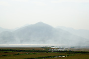 Smoke from smoldering crop burns in  fields with mountains in the background.