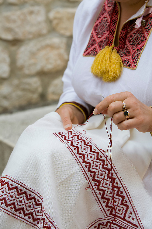 Europe, Croatia, Dalmatia, Dubrovnik. Woman in traditional clothing doing embroidery (torso only).  The historic center of Dubrovnik is a UNESCO World Heritage site.  MR