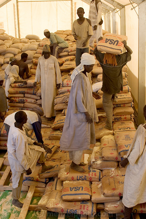 Workers stack bags of food aid at the Breidjing Refiugee Camp, run by the UN World Food Programme in eastern Chad. Food distribution at the Breidjing Refugee Camp is very systematic. Following a precise schedule, workers distribute food, including bags of corn-soy mixture and sorghum to block leaders, who then parcel it out to families.