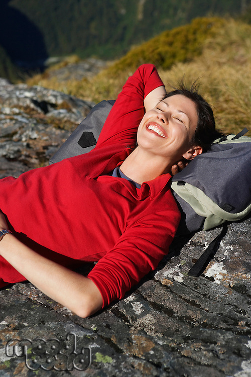 Woman laying on backpack on boulders