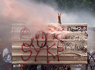 A protestor makes a V sign from behind a barrier while riot police use water cannon during clashes at Taksim Square in Istanbul, Turkey, 11 June 2013.<br /> Police used water cannon and tear gas on 11 June as they moved into Taksim Square, where two weeks of protests have been held, as some demonstrators threw rocks and Molotov cocktails. Authorities used construction machinery to clear barricades erected by the protesters around the central square as police entered it for the first time since 01 June after a crackdown on the demonstrations drew international condemnation.