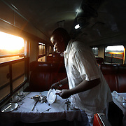"Waiters set the tables in the dining car of the Nairobi - Mombasa train as the sun rises. The approximately 300 mile journey took 16 hours this trip. Also known as the ""Lunatic Express"", It was the railway line that built Kenya, linking the port town of Mombasa through the capital, Nairobi, to the shores of Lake Victoria and on to the Ugandan capital, Kampala. It cost $5m (in 1894 money) and countless workers died during its construction. There were derailments, collisions, tribal raids and attacks by lions. Yet despite becoming one of Kenya's national treasures and a vital economic artery for east Africa, the railway now lies in a state of disrepair. A South African consortium has taken it over and plans to invest millions, returning it to its former glory. But there has been a row over the railway's financing which may yet derail the .project. .."