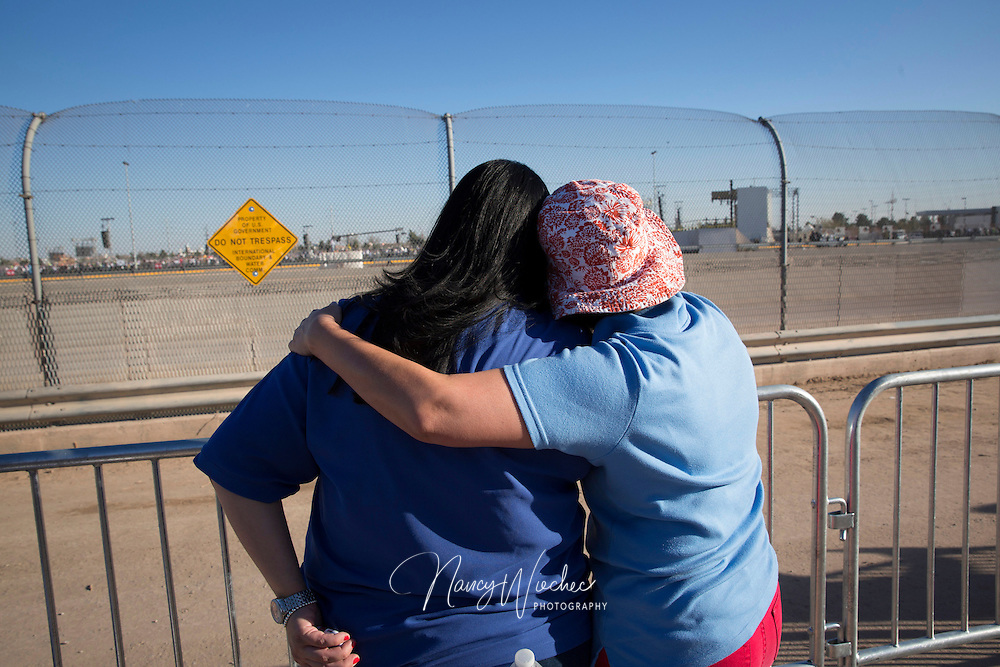 Women embrace as they watch the Mass with Pope Francis from the U.S. side of the border in El Paso, Texas, Feb. 17. The pope celebrated the final Mass of his Mexico visit in Ciudad Juarez. About 550 guests situated a levee north of the Rio Grande took part the service. (CNS photo/Nancy Wiechec)