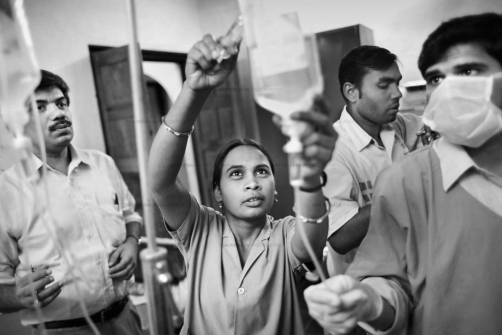 A nurse, watched by her colleagues, including Dr. Yogesh Jain (left) at the JSS hospital in Ganiyari, helps provide emergency medical treatment for a 30-year old woman experiencing seizures after attempting suicide by drinking insecticide. The woman is one of many such suicide cases treated at the JSS hospital in Ganiyari. She was brought to the hospital on a motorbike. After stabalising her, the JSS doctors admitted her to the ICU at the large government hospital in Bilaspur, 25km away. The woman survived thanks to the efforts of the JSS and was discharged from hospital one week later.<br />