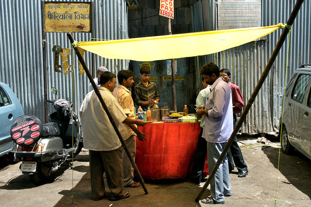 Office goers have lunch at a favorite food stall at the comercial district of Nariman Point in south Mumbai, June 2007