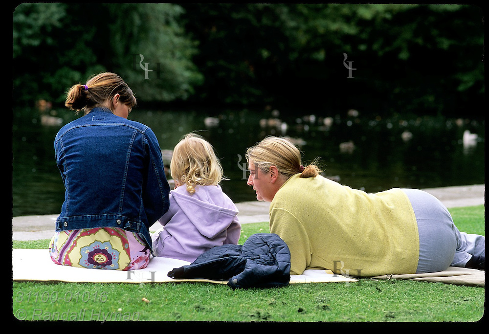 Mom, grandma and girl relax on blanket beside pond at St. Stephen's Green on a September afternoon; Dublin, Ireland.