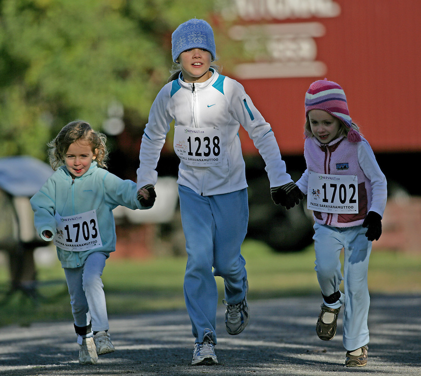 "(Ottawa (Cumberland), Ontario -- 11 Oct 2009) Jemima Saravanamuttoo (1703), Kendall Saravanamuttoo (1238) and Paige Saravanamuttoo (1702) competes in the 2009 Ottawa Fall Colours Marathon Turkey Trot 1km race for kids in Cumberland. [Photo credit should read ""Sean Burges / Mundo Sport Images""]"
