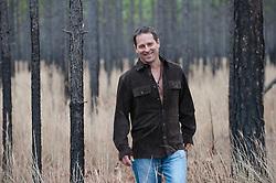 Man in a brown suede shirt walking through a grassy pine forest