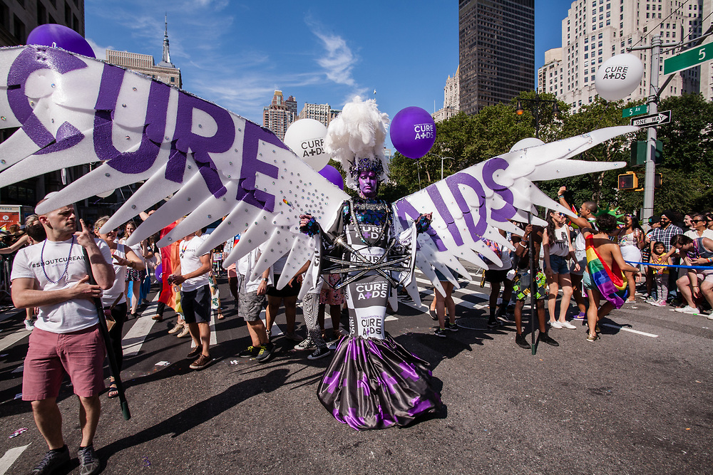 New York, NY - 25 June 2017. New York City Heritage of Pride March filled Fifth Avenue for hours with groups from the LGBT community and it's supporters. Marchers from the Research Foundation to Cure Aids are lead by a tall man in purple facepaint and with white wings that span two lanes of the street.