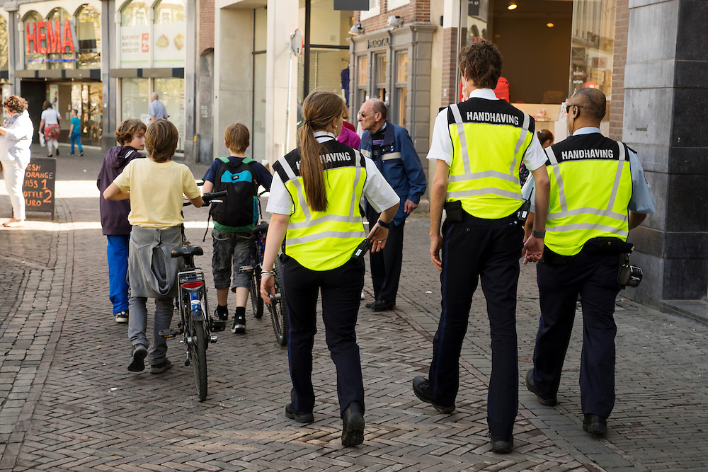 In Utrecht lopen drie jongetjes keurig met de fiets aan de hand door het voetgangersgebied in het centrum. Achter hen lopen drie medewerkers van de handhaving.<br /> <br /> In Utrecht, three boys walk nicely with the bike at the pedestrian area in the center. Behind them walk three employees of enforcement.