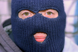 Portrait of teenage young offender wearing a balaclava,