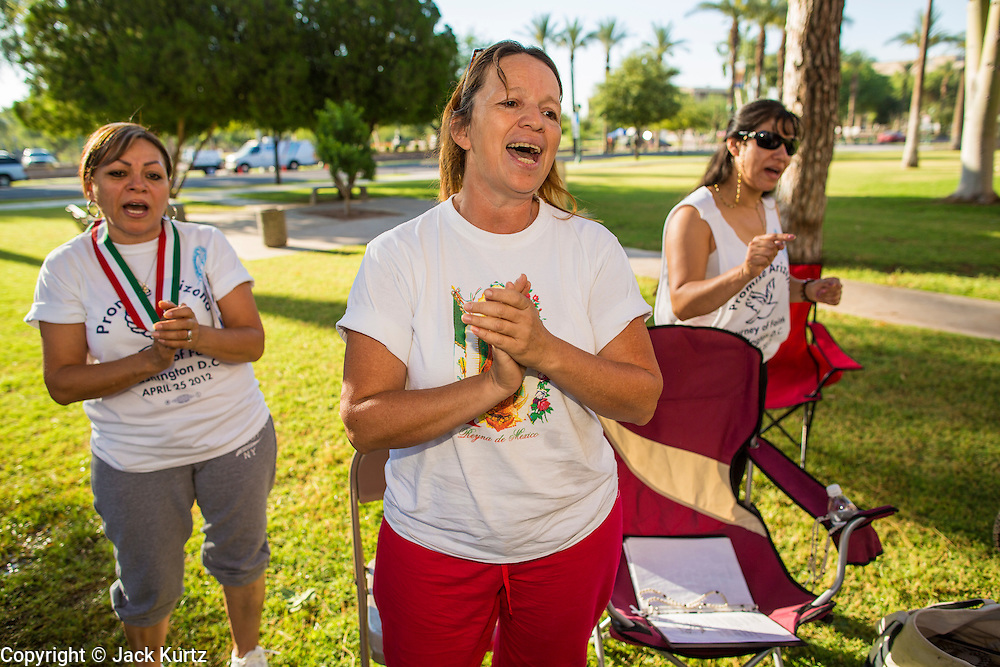 18 JUNE 2012 - PHOENIX, AZ: MARIA URIBE (center) and others pray that the US Supreme Court will overturn SB1070 Monday. About 20 people, members of the immigrant rights' group Promise AZ (PAZ) held a prayer vigil at the Arizona State Capitol in Phoenix Monday praying that the US Supreme Court would overturn SB 1070, Arizona's controversial anti-immigrant law. The court's ruling had been expected Monday, June 18 but the the court said the ruling would not come out until later this month. Members of PAZ said they would continue their vigil until the ruling was issued.    PHOTO BY JACK KURTZ