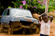 A girl stands by an old car in Tano Akakro, Cote d'Ivoire on Saturday June 20, 2009.