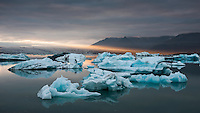 Golden evening rays backlight the blue icebergs on Jökulsárlón glacial lagoon. Jökulsárlón is situated in southeast Iceland, on the borders of Vatnajökull National Park. The lagoon stands 1.5 kilometres (0.93 mi) away from the ocean's edge and covers an area of about 18 km2 (6.9 sq mi). It recently became the deepest lake in Iceland at over 248 metres (814 ft) depth as glacial retreat extended its boundaries.