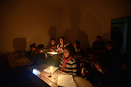 Aleppo, Syria, December, 2012 - A teacher and her class  the Al-Messarania Madrassa, a school that has been running without electricity and water for more then 20 days.  The Madrassa holds 80 students divided in 6 classes. Most of the time the rooms are freezing, with temperatures around 25 to 29 degrees Farenheit. (Photo by Miguel Juárez Lugo)