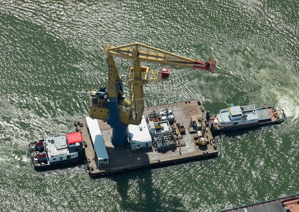 Drijf kraan Marcor met duwboot en sleepboot wordt in positie gebracht bij te lossen schip in de Waalhaven