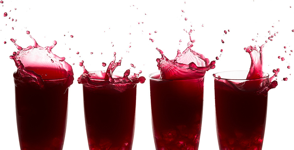 Sequence of splashes on raspberry juice against a white background