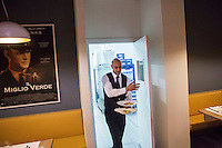 "MILANO, ITALY - 1 MARCH 2016: Said Manah, an inmate and waiter, steps outside of the kitche to serve dinner to customers of the ""InGalera"" restaurant in the Bollate prison in Milan, Italy, on March 1st 2016.<br /> <br /> ""InGalera"" (which translates in English as ""InJail"") is the first restaurant located inside a prison and offering high-quality cooking to the public and a future to the inmates. It was inaugurated last October inside the Bollate prison in Milan. It is open five days a week for lunch and dinner, and seats 55 people. There are 9 people involved in the project, including cooks and waiters, all regularly employed and all inmates of the prison, apart from the chef and the maître d'hôtel, recruited from outside to guarantee the high quality of the food served. The restaurant is a project of the co-operative ABC La Sapienza - that operates inside the prison and provides more than 1,000 meals three times a day with the help of inmates they've hired - and of PwC, a multinational operating in the field of corporate consultancy. The goal of this project is to follow prisoners in rehabilitation process of social inclusion.<br /> <br /> The Bollate prison is already known for being a good example of penitentiary administration. The inmates are free to move around from one area to the other inside the prison (their cells open at 7:30am and close at 9pm) to go study, exercise in a gym, or work (in a call center, as scenographers, tailors, gardeners, cooks, typographers, among others)  in one of the 11 co-operatives inside the prison or in one of the private partnering businesses outside the prison. The turnover of the co-operatives that work inside the prison was €2mln in 2012."