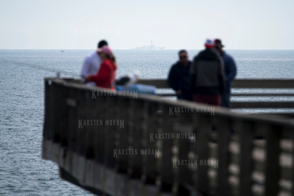 March 19, 2018 - San Diego, Calif. : A U.S. Navy ship can be seen on the horizon behind people fishing on the Ocean Beach pier in San Diego.  CREDIT: Karsten Moran / Redux