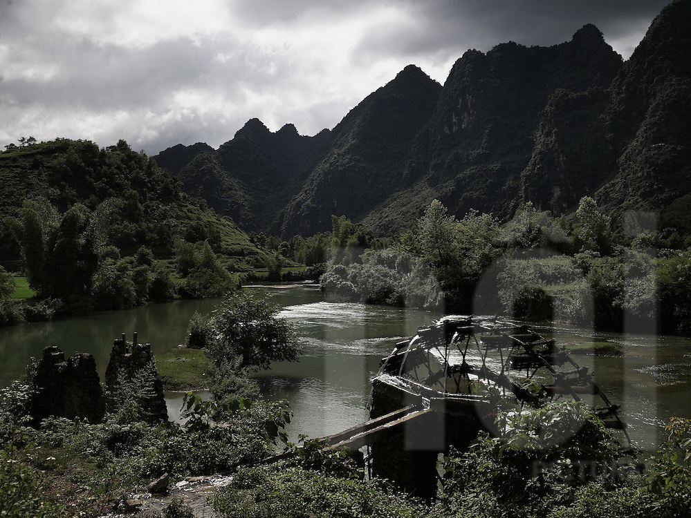 Mountainous landscape with a river flowing in the valley. An old watermill is built along the stream bank. Cao Bang province, Vietnam, Asia.