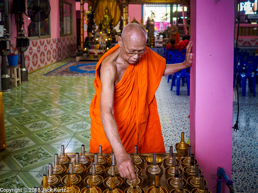 "14 FEBRUARY 2018 - BANG KRUAI, NONTHABURI, THAILAND: A Buddhist monks sets out holy water used in prayers before a resurrection ceremony at Wat Ta Khien, about 45 minutes from Bangkok in Nonthaburi province. The temple is famous for the ""floating market"" on the canal that runs past the temple and for the ""resurrection ceremonies"" conducted by monks at the temple. People lie in a coffin and ritualistically die before being reborn. Adherents believe it will improve their karma and help make up for past sins.         PHOTO BY JACK KURTZ"