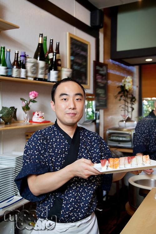 Portrait of mature chef with Japanese cuisine