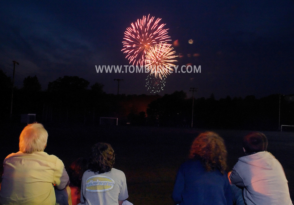 Monroe, N.Y. - A family watches fireworks from Smith Clove Park during a Fourth of July celebration on July 3, 2006. ©Tom Bushey