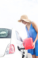 Woman refueling car against clear sky on sunny day