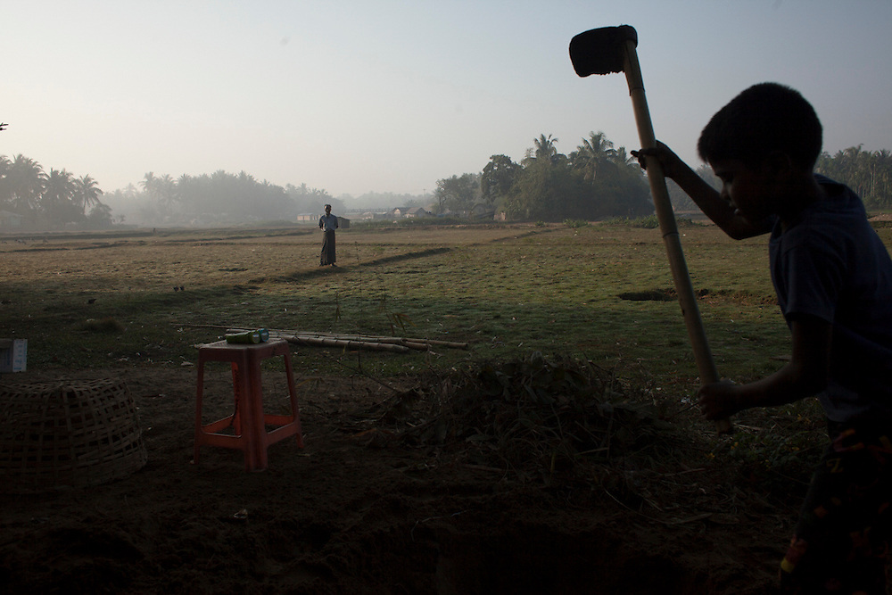 A Rohingya boy works while a man watches in an IDP camp in Sittwe, Myanmar.