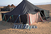 Portable solar panels used to produce electric power for cooking outside a traditional Berber nomad´s tent, Sahara desert, near Zagora, Morocco