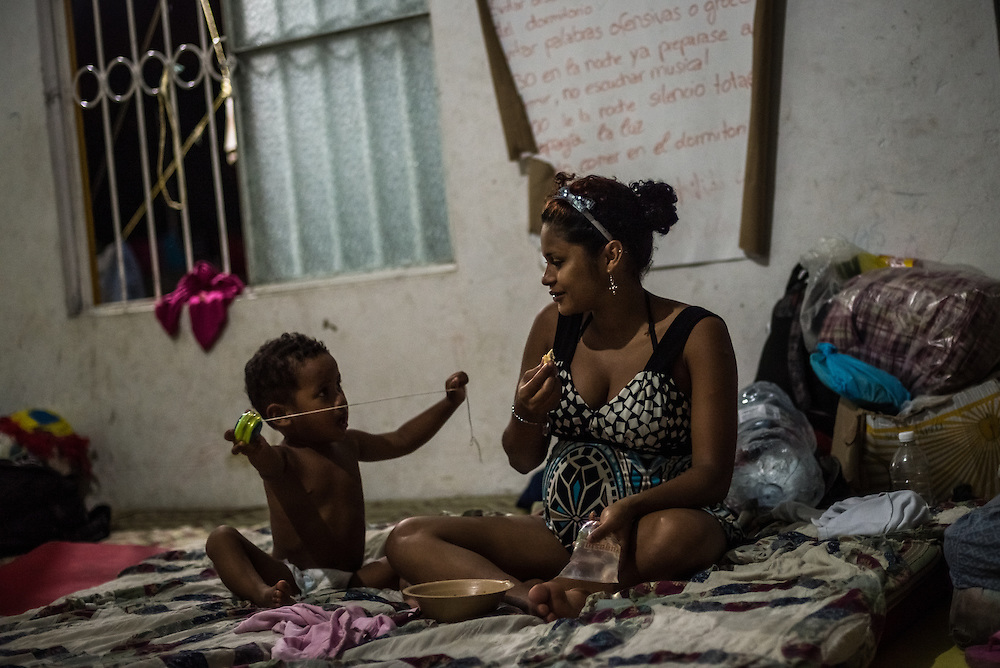 TENOSIQUE, MEXICO - MAY 29, 2014:  A woman from Honduras who is 8-months pregnant and plans to migrate north soon with her young son, rests at the 72 migrant shelter in Tenosique, where  Catholic priests and other volunteers provide mats for migrants to sleep on, second-hand clothes, meals, basic medical treatment, and help applying for immigration visas and refugee status to people traveling north. The shelter, which traditionally has been visited by men between the ages of 15-35, has been overrun by women and children in recent months, more than double the amount -- consequential of a recent boom of minors headed to the United States from Central America. PHOTO: Meridith Kohut for The New York Times