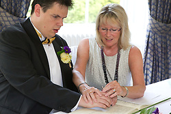 Visually impaired groom being helped to sign register by the registrar.