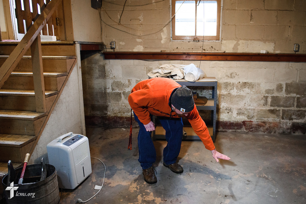 Paul Wellborn indicates on Saturday, Jan. 9, 2016, how high the water reached in his basement in Watseka, Ill., during a recent flood in December that affected a large swath of the town.  LCMS Communications/Erik M. Lunsford