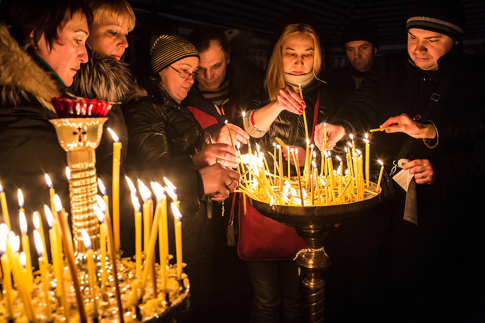 KIEV, UKRAINE - FEBRUARY 23: People light candles inside a tent serving as a chapel in Independence Square on February 23, 2014 in Kiev, Ukraine. After a chaotic and violent week, Viktor Yanukovych has been ousted as President as the Ukrainian parliament moves forward with scheduling new elections and establishing a caretaker government. (Photo by Brendan Hoffman/Getty Images) *** Local Caption ***