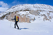 Backcountry skier crossing Mack Lake in Little Lakes Valley, Inyo National Forest, Sierra Nevada Mountains, California