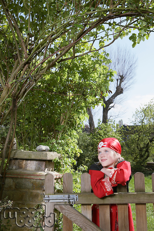 Portrait of young boy (7-9) wearing pirate costume leaning on garden gate