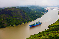 Blue oil tanker traveling between terraced banks underway to the Panama Canal.