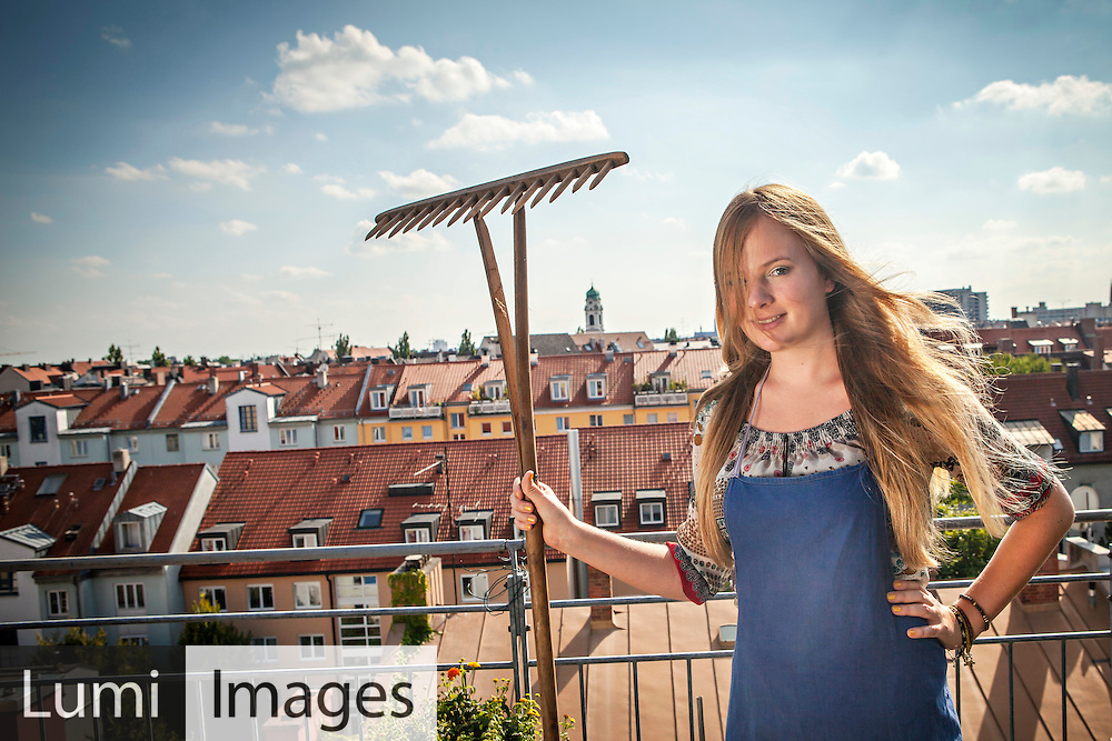 Woman On Roof Terrace Holding Garden Rake, Munich, Bavaria, Germany, Europe