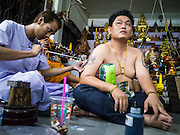 "22 MARCH 2013 - NAKHON CHAI SI, NAKHON PATHOM, THAILAND: A man gets a sacred Sak Yant tattoo at Wat Bang Phra. Wat Bang Phra is the best known ""Sak Yant"" tattoo temple in Thailand. It's located in Nakhon Pathom province, about 40 miles from Bangkok. The tattoos are given with hollow stainless steel needles and are thought to possess magical powers of protection. The tattoos, which are given by Buddhist monks, are popular with soldiers, policeman and gangsters, people who generally live in harm's way. The tattoo must be activated to remain powerful and the annual Wai Khru Ceremony (tattoo festival) at the temple draws thousands of devotees who come to the temple to activate or renew the tattoos. People go into trance like states and then assume the personality of their tattoo, so people with tiger tattoos assume the personality of a tiger, people with monkey tattoos take on the personality of a monkey and so on. In recent years the tattoo festival has become popular with tourists who make the trip to Nakorn Pathom province to see a side of ""exotic"" Thailand. The 2013 tattoo festival was on March 23.    PHOTO BY JACK KURTZ"