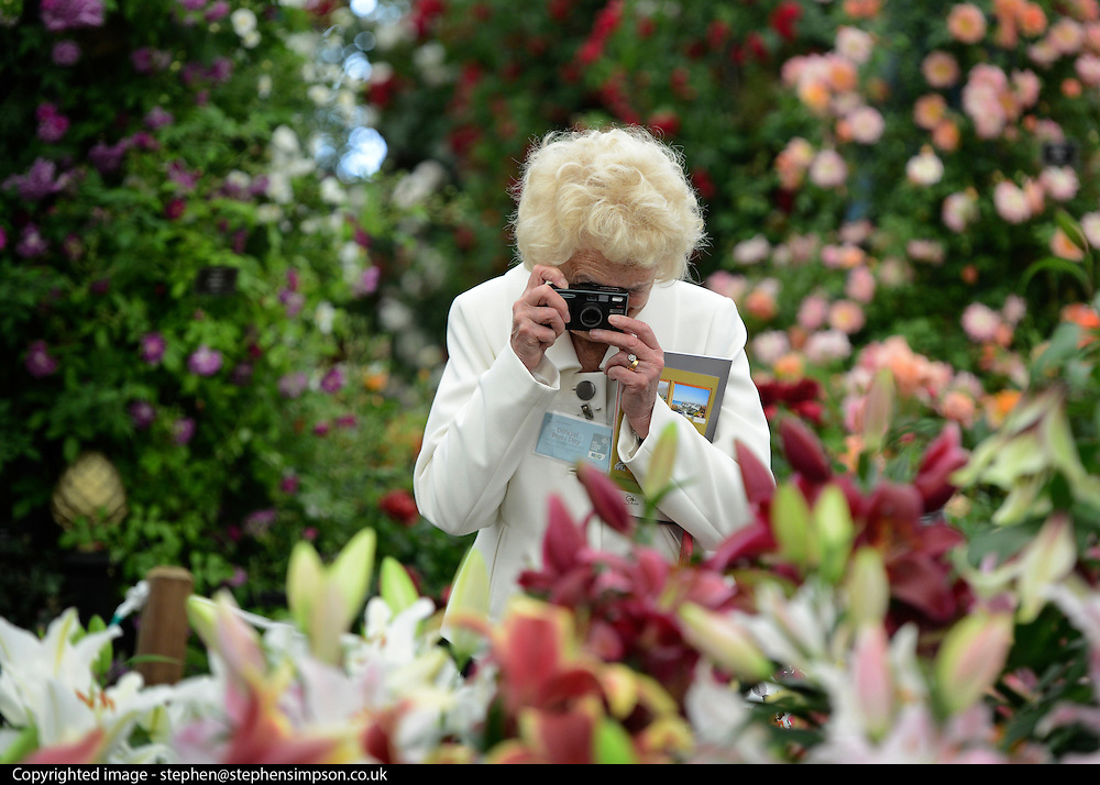 © Licensed to London News Pictures. 21/05/2012. Chelsea, UK. A woman photographs a display of flowers.  Press preview of The Chelsea Flower Show today 21 May 2012. The world's most famous flower show, which has been held in the grounds of the Royal Chelsea Hospital since 1913, will be open to the public from Tuesday. Visitors are expected to flock in their thousands to see displays of plants, flowers and furniture for ideas on how to decorate their gardens.. Photo credit : Stephen Simpson/LNP