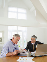 Senior man sitting at table with financial advisor