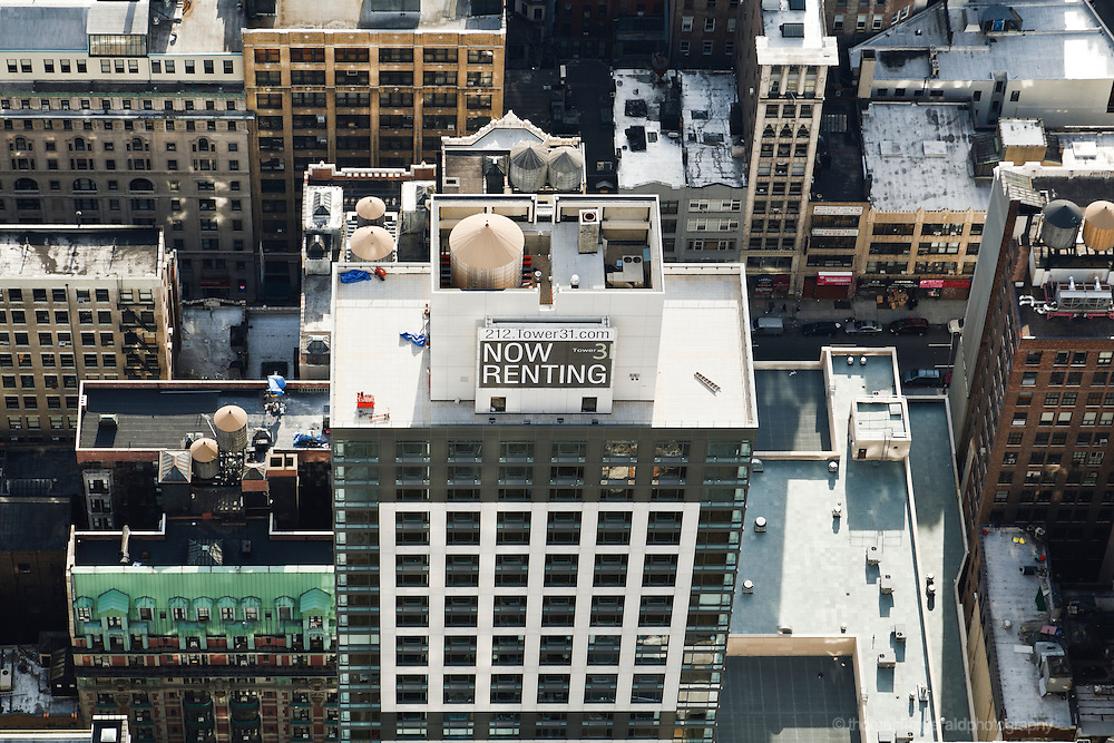 Looking down on the rooftops of various NYC buildings and the streets below