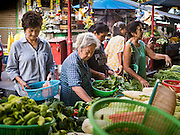 14 DECEMBER 2015 - BANGKOK, THAILAND:  Women shop for produce in Bang Chak Market. The market closes permanently on Dec 31, 2015. The Bang Chak Market serves the community around Sois 91-97 on Sukhumvit Road in the Bangkok suburbs. About half of the market has been torn down. Bangkok city authorities put up notices in late November that the market would be closed by January 1, 2016 and redevelopment would start shortly after that. Market vendors said condominiums are being built on the land.      PHOTO BY JACK KURTZ